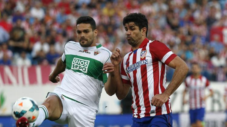 Atletico Madrid's Costa and Elche's Botia fight for the ball during their Spanish first division soccer match at Vicente Calderon stadium in Madrid
