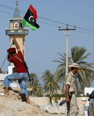 Libyan fighter plants the Libya's flag of the former rebels at a check point in Al Ajaylat, 120 km west of Tripoli, Libya, Wednesday, Sept. 7, 2011.  The new colours of the flag decorate a lot of streets and buildings after the six-month civil war that ended Gadhafi's 42-year rule and sent him into hiding. (AP Photo/Francois Mori)