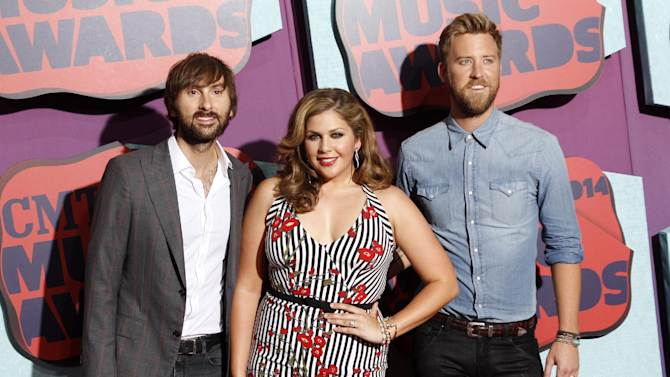 """FILE - In this June 4, 2014 file photo, members of Lady Antebellum, from left, Dave Haywood, Hillary Scott and Charles Kelley arrive at the CMT Awards in Nashville,Tenn. The bands latest release, """"747,"""" was released this week. (Photo by Wade Payne/Invision/AP, File)"""