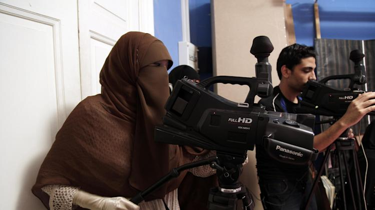 "Heba Seraj, left, and Mohy Abozeid, right, film a segment of a Ramadan program at the Maria Channel's studio in Cairo, Egypt, Monday, July 23, 2012. The first Egyptian satellite channel operated by women wearing the niqab, or face veil, launched on the first day of the holy month of Ramadan. The station manager says he hopes the full face-veiled women will set an example for others by showing a ""new kind of woman"" as a role model.(AP Photo/Maya Alleruzzo)"