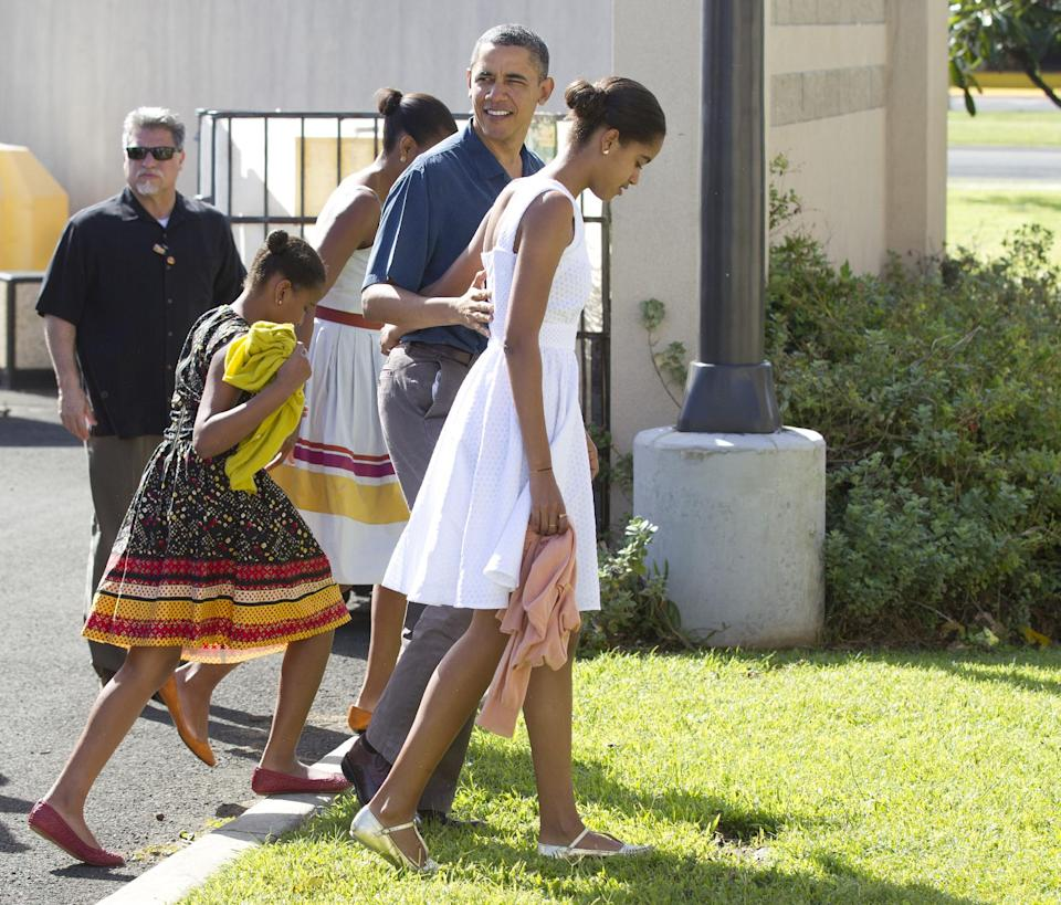 President Barack Obama, first lady Michelle Obama and their daughters Malia and Sasha arrive for Christmas service at the Kaneohe bay Chapel on Marine Corps Base Hawaii , Sunday, Dec. 25, 2011, in Kaneohe, Hawaii. (AP Photo/Carolyn Kaster)