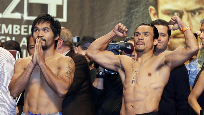 Manny Pacquiao, left, and Juan Manuel Marquez react to the crowd after the weigh-in for their welterweight fight, Friday, Dec. 7, 2012, in Las Vegas. The pair face off in their fourth fight against each other on Saturday in Las Vegas. (AP Photo/Julie Jacobson)