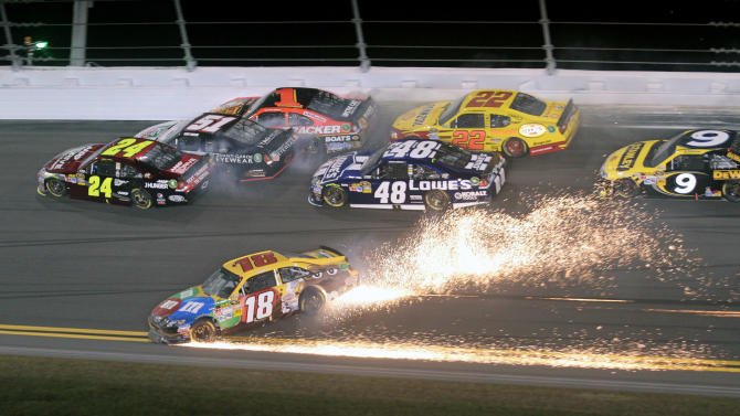 Kyle Busch (18) slides sideways to avoid a wreck as Jeff Gordon (24) heads to the wall before his car slid on its side and then rolled, during the NASCAR Budweiser Shootout auto race at Daytona International Speedway, Saturday, Feb. 18, 2012, in Daytona Beach, Fla. Busch won the race. (AP Photo/Bill Friel)