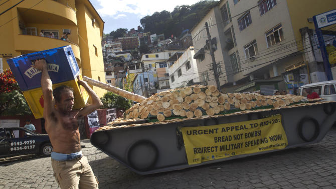 """A worker carries crates past a fake life-sized war tank covered with bread sitting on display in the Santa Marta slum as part of a """"Bread not Bombs"""" protest on the sidelines of the Rio+20 UN Conference on Sustainable Development in Rio de Janeiro, Brazil, Tuesday, June 19, 2012. Activists placed the fake war tank covered with bread for residents to eat and to demand leaders at the Rio+20 to redirect military spending to pay for basic needs. (AP Photo/Silvia Izquierdo)"""