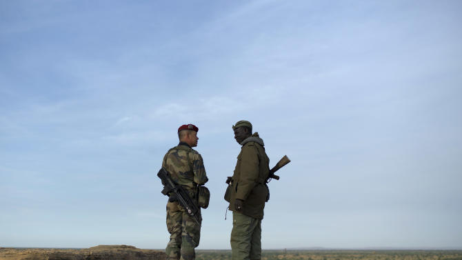 A French soldier, left, talks with a Malian soldier during a patrol in the outskirts of Sevare, Mali, some 620 kms (385 miles) north of Bamako, Wednesday, Jan. 23, 2013. The U.S. airlift of French forces to Mali to fight Islamic extremists is expected to go on for another two weeks, Pentagon officials said, as hundreds of African troops from Nigeria, Togo, Burkina Faso and Senegal are now joining the French-led intervention. (AP Photo/Thibault Camus)