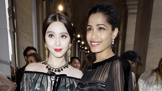 L'Oreal girl Fan Bing Bing, left, and actress Frida Pinto arrive for the Salvatore Ferragamo Cruise 2013 fashion show at Louvre Museum in Paris, France, Tuesday, June 12, 2012. (AP Photo/Francois Mori)