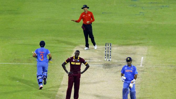 West Indies captain Jason Holder reacts as India's Suresh Raina scores four runs alongside MS Dhoni during their Cricket World Cup win over the West Indies in Perth