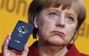 German Chancellor Merkel holds a BlackBerry Z10 smartphone featuring high security Secusite software at the booth of Secusmart during her opening tour at the CeBit computer fair in Hanover