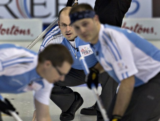 Quebec skip Menard watches the line of his shot as teammates Philippe Menard and Sylvain sweep during play at the Canadian Men's Curling Championships in Edmonton