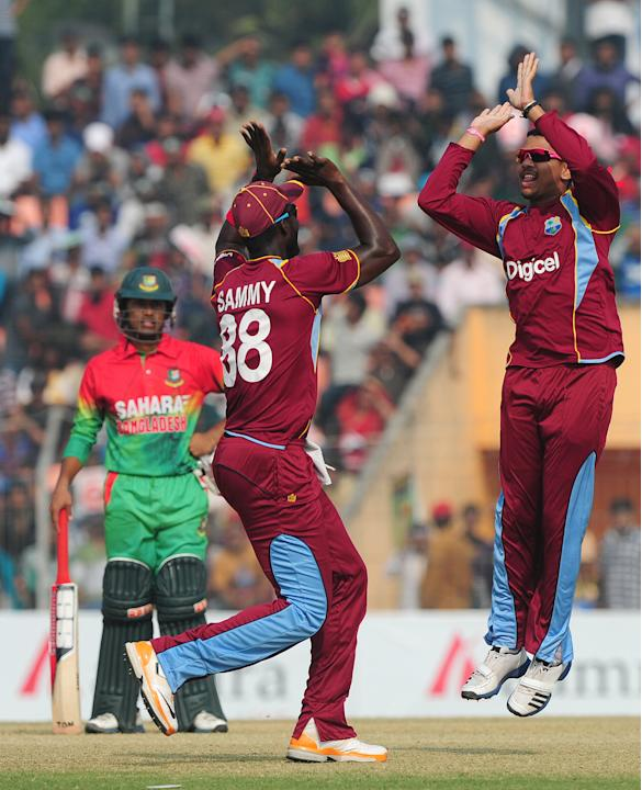 West Indies cricketer Sunil Narine (R) celebrates with his captain Darren Sammy (C) after the dismissal of the unseen Bangladesh cricketer Tamim Iqbal during the first one day international cricket ma