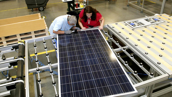 In this Sept. 4, 2012 photo, Stacey Rassas, right, a quality control manager at a Suntech Power Holdings Co., a Chinese-owned solar panel manufacturer, examines a solar panel with her co-worker Frank Garcia at a company facility in Goodyear, Ariz. The factory makes solar panels for one of the world's biggest solar manufacturers. (AP Photo/Ross D. Franklin)