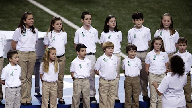 "Students from Sandy Hook Elementary School sing ""America the Beautiful"" before the NFL Super Bowl XLVII football game between the San Francisco 49ers and the Baltimore Ravens, Sunday, Feb. 3, 2013, in New Orleans. (AP Photo/Charlie Riedel)"