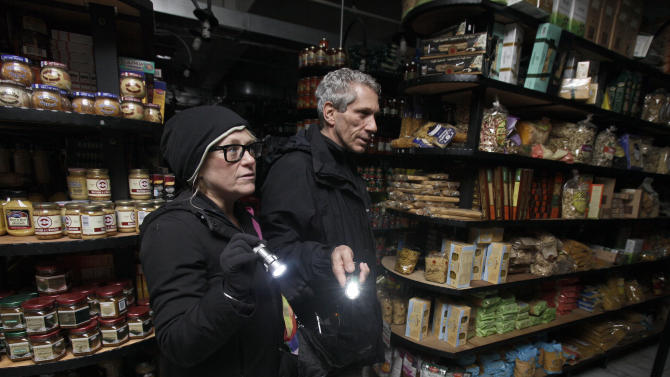 In this Tuesday, Oct. 30, 2012 photo, a couple shops for groceries by flashlight in the Tribeca neighborhood of New York, following a loss of power due to Superstorm Sandy. The U.S. economy added a solid 146,000 jobs in November and the unemployment rate fell to 7.7 percent, the lowest since December 2008, the Labor Department announced Friday, Dec. 7, 2012. The government said Superstorm Sandy had only a minimal effect on the figures. (AP Photo/Richard Drew)