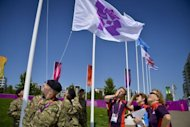 Volunteers watch soldiers raising a flag during the flag raising ceremony at the Olympic village in London on July 23. A 70,000-strong volunteer army from across the globe is helping to put on the 2012 Olympics, giving up their free time or holidays in return for a part in the biggest show on Earth
