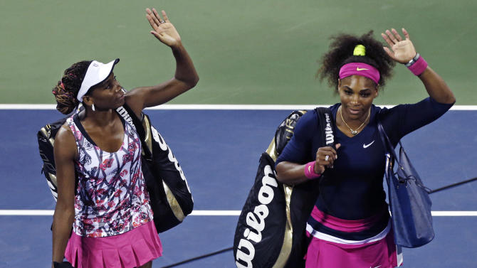 Venus Williams, left, and Serena Williams wave as they walk off the court following their 6-1, 6-4 loss to Russia's Maria Kirilenko and Nadia Petrova in their match during the third round of women's doubles play at the U.S. Open tennis tournament, Monday, Sept. 3, 2012, in New York. (AP Photo/Charles Krupa)