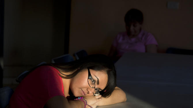 In this May 18, 2013 photo, Adriana Gil Diaz, 22, sits inside the kitchen of the San Juan Bosco Migrant Shelter where she volunteers in Nogales, northern Mexico. Gil Diaz was taken by her mother to the United States without authorization when she was a baby, and grew up and went to school in Phoenix, Arizona. At age 20, she decided to return to her native Mexico where she could afford to attend college. But nearly two years later, unforeseen bureaucratic hurdles have blocked her from enrolling, and she's run out of money. She also missed her chance at qualifying for legal status in the United States. (AP Photo/Nick Oza)
