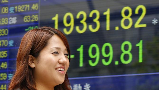 A woman walks past an electronic stock indicator of a securities firm in Tokyo, Thursday, May 7, 2015. Asian markets drooped Thursday after comments from the U.S. Federal Reserve chief fanned fears about the American economy and sent Wall Street lower. (AP Photo/Shizuo Kambayashi)