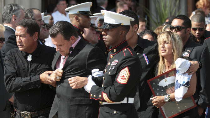 Lance Cpl. Greg Buckley Jr.'s father Greg, foreground, and mother Marina are escorted from St. Agnes Cathedral after his funeral Mass, Saturday, Aug. 18, 2012, in Rockville Center, N.Y..  Buckley Jr. was barely 21 years old when he was killed in an attack by a policeman in Afghanistan. (AP Photo/Mary Altaffer)