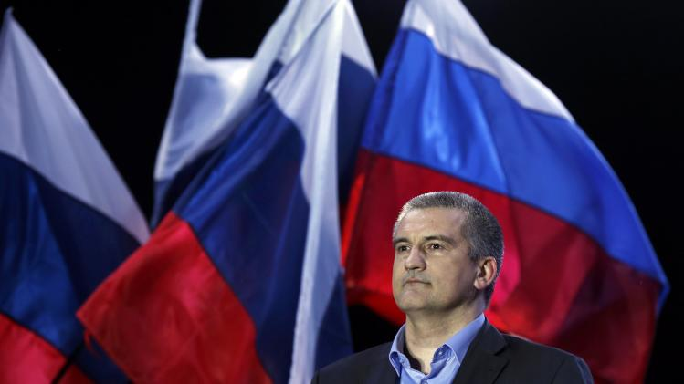 Crimean PM Aksyonov stands on a stage as preliminary results of today's referendum are announced on Lenin Square in the Crimean capital of Simferopol