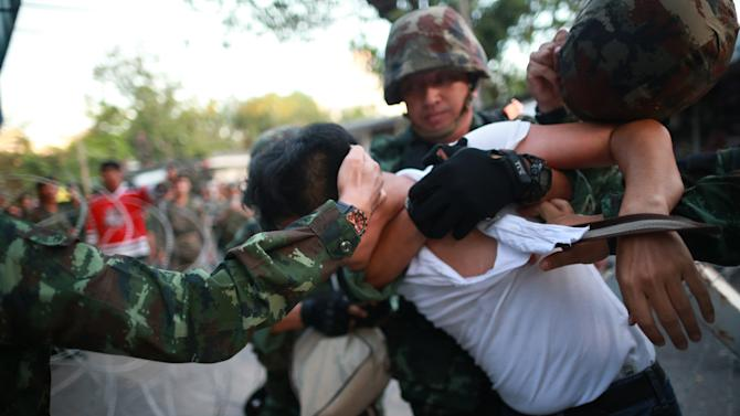 "A protester is detained by Thai soldiers during an anti-coup demonstration at the Victory Monument in Bangkok, Thailand, Saturday, May 24, 2014. Thailand's coup leaders said Saturday that they would keep former Prime Minister Yingluck Shinawatra, Cabinet members and anti-government protest leaders detained for up to a week to give them ""time to think"" and to keep the country calm. They also summoned outspoken academics to report to the junta. (AP Photo/Wason Wanichakorn)"