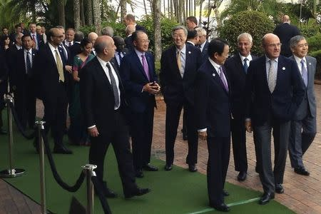Delegates of the G20 Finance Ministers and Central Bank Governors Meeting talk as they arrive for an official photograph in the northern Australian city of Cairns