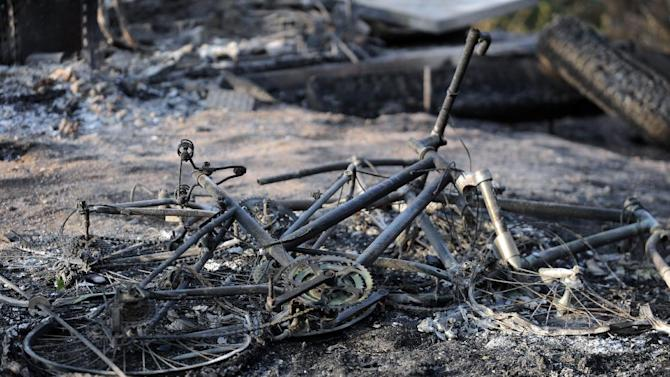 The remains of a mountain bike lays in the ashes outside a house along Holmes Road Thursday, June 13, 2013, during the third day of the Black Forest Fire north of Colorado Springs, Colo.(AP Photo/The Gazette, Christian Murdock) MAGS OUT