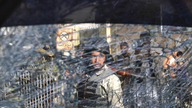 An Afghan soldier passes by a chattered window of a destroyed police car after an explosive device went off in the center of Jalalabad, east of Kabul, Afghanistan, Tuesday, March 6, 2012. The explosion wounded three policemen. (AP Photo/Rahmat Gul)