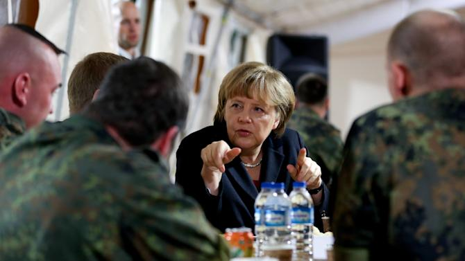 German Chancellor Angela Merkel , center, meets  German soldiers in Kahramanmaras, Turkey Sunday Feb. 24, 2013.  German Chancellor Angela Merkel is visiting German troops deployed to operate Patriot missile batteries in Turkey. The Patriots were sent to Turkey, a NATO member, to protect it from spillover from Syria's civil war. Merkel's two-day visit comes as Turkey grows increasingly frustrated over the slow progress in its bid for European Union membership. Before arriving Sunday, Merkel said she backs opening a new chapter in those stalled talks, despite being skeptical about Turkey's accession.  The chancellor's first stop was Kahramanmaras, some 100 kilometers (60 miles) from the Syrian border, where some 300 German troops are manning two out of six NATO-deployed anti-missile batteries. (AP Photo/dpa, Kay Nietfeld)