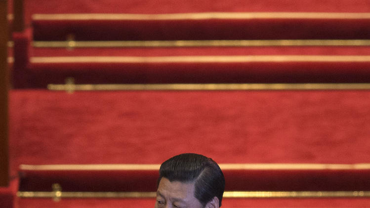 Chinese President Xi Jinping claps while he arrives at a plenary session of the National People's Congress in Beijing's Great Hall of the People, China, Saturday, March 16, 2013. China's new leaders turned Saturday to veteran technocrats with greater international experience to staff a Cabinet charged with overhauling a slowing economy and pursuing a higher global profile without triggering opposition. (AP Photo/Alexander F. Yuan)
