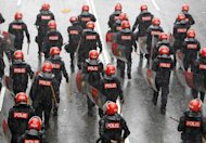 Malaysian riot police officers march on a street under heavy rain during a rally in Kuala Lumpur, Malaysia, Saturday, July 9, 2011. Police fired tear gas and detained hundreds of activists as those demonstrators massed Saturday across Malaysia's main city demanding electoral reforms in the country's biggest political rally in years. (AP Photo/Vincent Thian)