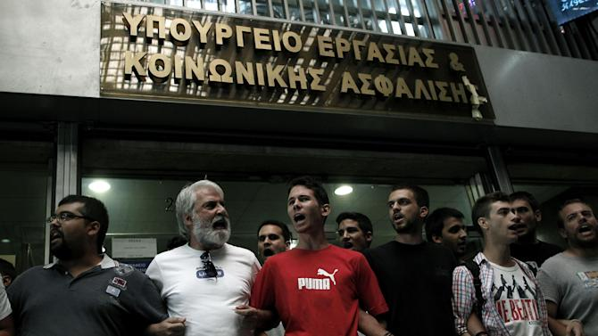 Communist-backed unionists holding flags and chanting slogans, Block access to the ministry building in Athens, Greece, on Tuesday, Sept. 11, 2012. The protest came ahead of a visit there by debt inspectors monitoring Greece's austerity program. Debt-crippled Greece has been kept afloat by international rescue loans since 2010, in return for big spending cuts.  The conservative-led coalition government is working to finalize a new 11.5 billion Euro (14.7 billion US dollars) austerity program for 2013-14.(AP Photo/Petros Giannakouris)