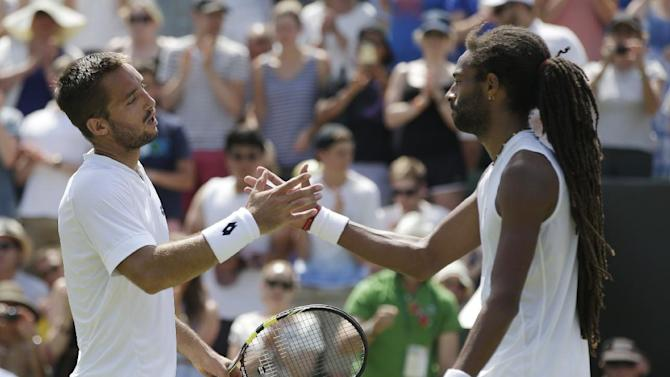 Viktor Troicki of Serbia, left, shakes hands after defeating Dustin Brown of Germany in their singles tennis match at the All England Lawn Tennis Championships in Wimbledon, London, Saturday July 4, 2015. Troicki  won the match 6-4, 7-6, 4-6, 6-3. (AP Photo/Pavel Golovkin)