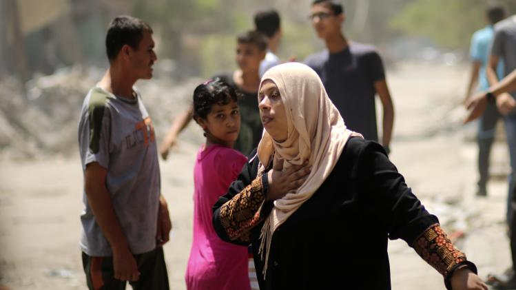 A Palestinian woman fleeing from her house reacts following what witnesses said was an Israeli air strike in Gaza City