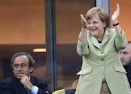 German Chancellor Angela Merkel (R) celebrates next to UEFA president Michel Platini (L) after Philip Lahm scored against Greece during the Euro 2012 football championships quarter-final match Germany vs Greece on June 22, 2012 at the Gdansk Arena.   AFP PHOTO / FABRICE COFFRINI