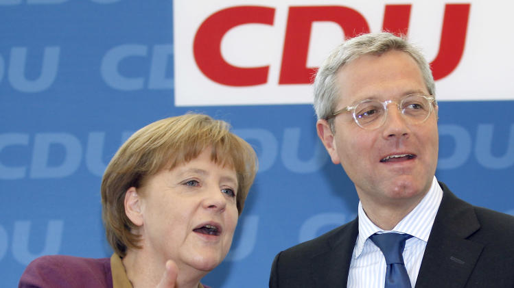 German Chancellor Angela Merkel, left, talks with the party's top candidate for the state elections in North Rhine-Westphalia, Norbert Roettgen, at the beginning of a board meeting of the German Christian Democratic party in Berlin, Germany, Monday, May 14, 2012. Merkel's CDU party faced big losses at the elections in Germany's most important and populous state Sunday evening. (AP Photo/Michael Sohn)