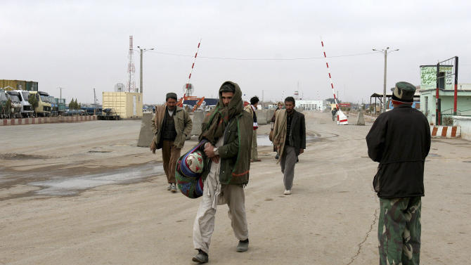 FILE - In this Jan. 11, 2006 file photo, men return to Afghanistan from Iran at Islam Kala, the largest border crossing in western Afghanistan, near Herat. A former Bush administration official told the AP in 2008 that Iran had rounded up hundreds of Arabs who had crossed the border from Afghanistan, expelled many of them and made copies of nearly 300 of their passports in an effort to help the U.S. counter al-Qaida after Sept. 11, 2001. It was a moment of rare common purpose between Iran and Washington that could have opened doors for greater diplomatic overtures. (AP Photo/Hasan Sarbakhshian, File)