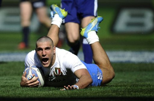 Italy's Giovanbattista Venditti (C) scores a try against Scotland
