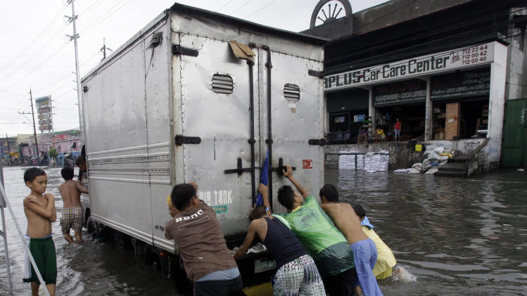 Men push a truck in the flooded street for a fee Tuesday, Aug. 2, 2011 in suburban Quezon City, north of Manila, Philippines.  Waist-deep floods have swamped the streets in the Philippine capital after a night of monsoon rains closed down schools and government offices. (AP Photo/Pat Roque)