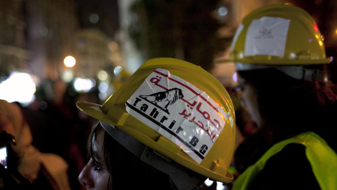 "Two Egyptian volunteers of Tahrir Bodyguard, an anti-harassment group, look on during a protest for women against sexual harassment and against the Islamist dominated Shura Council blaming women for the attacks against them, in Cairo, Egypt, Tuesday, Feb. 12, 2013. Arabic on the helmet reads ""protecting Tahrir."" (AP Photo/Nasser Nasser)"