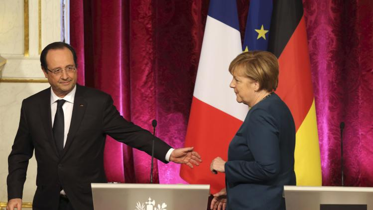 French President Hollande and German Chancellor Merkel leave a press conference at the Elysee Palace in Paris,