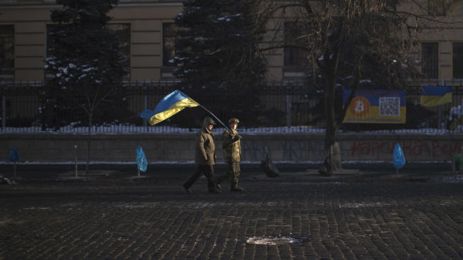 Opposition supporters, one of them holding a Ukrainian flag, walk along a street heading to Kiev's Independence Square, the epicenter of the country's current unrest, Ukraine, Monday, Feb. 3, 2014. Ukraine's president will return Monday from a short sick leave that had sparked a guessing game he was taking himself out of action in preparation to step down or for a crackdown on widespread anti-government protests. (AP Photo/Emilio Morenatti)