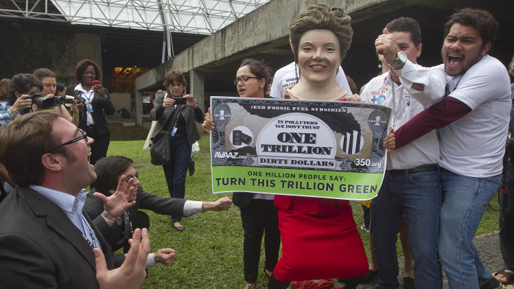 "Environmental activists, one portraying Brazilian President Dilma Rousseff holding a banner symbolizing ""dirty money"" made from fossil fuel subsidies, protest on the final day of the United Nations Conference on Sustainable Development, or Rio+20, in Rio de Janeiro, Brazil, Friday, June 22, 2012. (AP Photo/Andre Penner)"