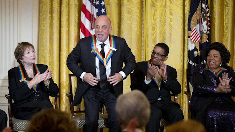 Recipient of the 2013 Kennedy Center Honors, Billy Joel, second from left, stands and acknowledges the applause by fellow honorees Shirley MacLaine, left, Herbie Hancock, second from right, and Martina Arroyo, during a reception honoring the 2013 Kennedy Center Honors recipients, in the East Room of the White House in Washington, Sunday, Dec. 8, 2013. (AP Photo/Manuel Balce Ceneta)