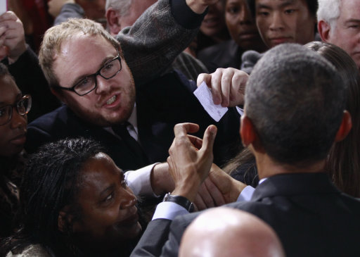 A protester, wearing glasses, hands President Barack Obama a note as the president greeted audience members after speaking about jobs, Tuesday, Nov. 22, 2011, at Manchester High School Central in Manchester, N.H. (AP Photo/Charles Dharapak)
