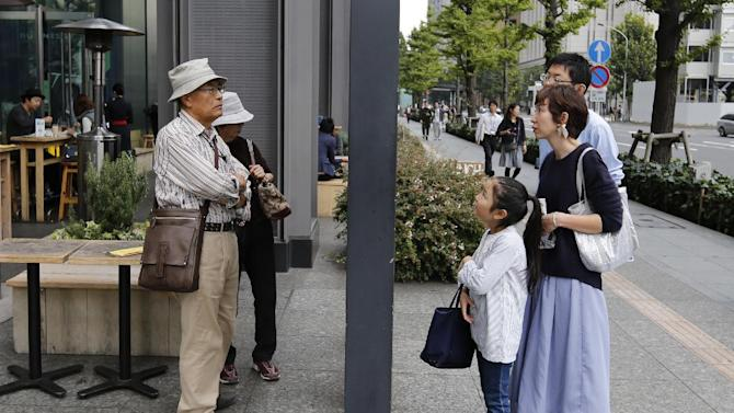 Tourists look at the guide map of a town in Tokyo, Sunday, Oct. 26, 2014. (AP Photo/Shizuo Kambayashi)