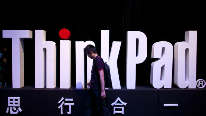 A man walks past a ThinkPad logo during a promotional event for the new Thinkpad X1 Carbon laptop in Beijing Monday, Aug. 6, 2012. The Chinese computer maker unveiled the lighter, quicker ThinkPad notebook computer inspired by the convenience of tablets and smart phones. (AP Photo/Alexander F. Yuan)