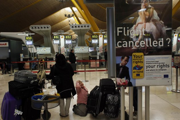 Passengers wait for help after more than 80 Iberia flights were cancelled due to a strike, at Madrid's Barajas airport