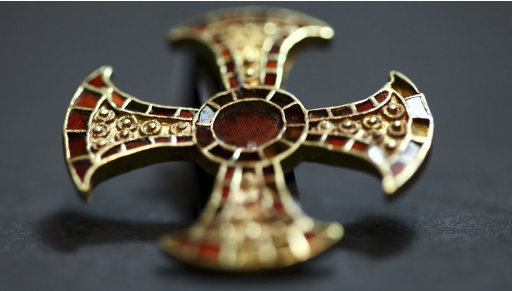 In this undated image made available by the University of Cambridge in England early Friday March 16, 2012,  shows a cross.  Archaeologists excavating near Cambridge have stumbled upon a rare and mysterious find,  the skeleton of a 7th-Century teenager buried in an ornamental bed along with a gold-and-garnet cross, an iron knife and a purse of glass beads.  There is very little known about this funerary practice, which one archaeologist, Alison Dickens, said would open a window of knowledge into the transitional period when the pagan Anglo-Saxons were gradually adopting Christianity. (AP Photo/University of Cambridge)