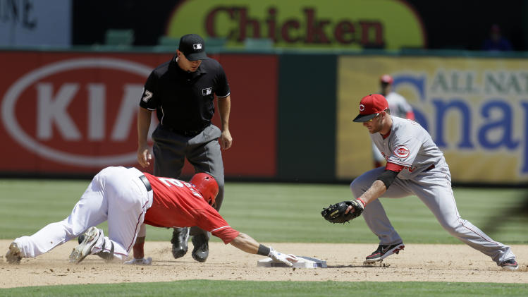 Texas Rangers' Leonys Martin is able to hold on to the bag for a double under pressure from Cincinnati Reds' Zack Cozart as base umpire Scott Barry, rear, watches before making the call in the fifth inning of a baseball game Sunday, June 30, 2013, in Arlington, Texas. (AP Photo/Tony Gutierrez)