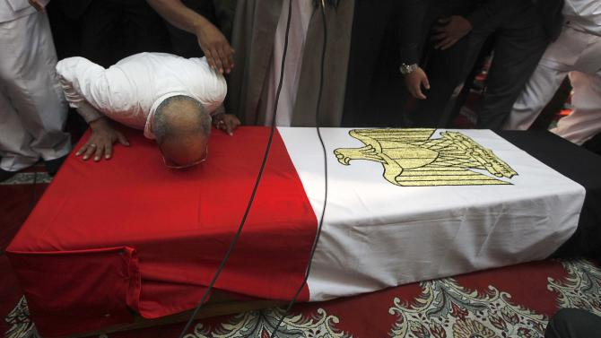 A mourner kisses the coffin of Police General Farag during his funeral service at Al-Rashdan Mosque in Nasr City